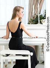 Back view of female pianist sitting and playing piano - Back...