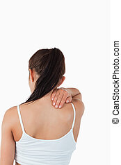 Back view of female with pain in her neck against a white...