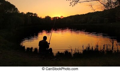 back view of fisherman stringing bait and casting the line ...