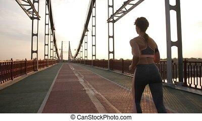 Back view of fit senior female runner on bridge