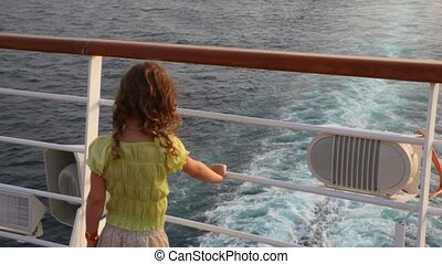 back view of girl stands aft of cruise ship