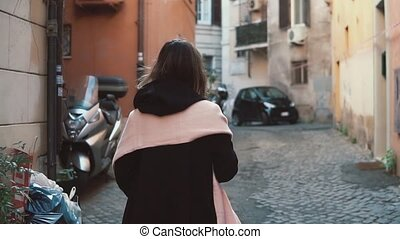 Back view of girl walking alone in old town. Brunette woman going through the street. Female have vacation in Europe.