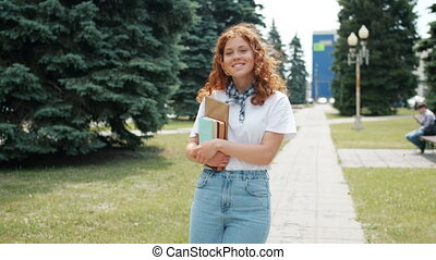 Back view of girl walking outdoors holding books then turning to camera smiling