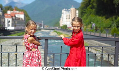 Back view of girls on the embankment of a mountain river in a European city.