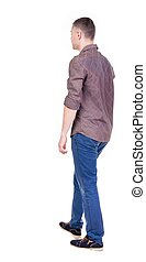 Back view of going handsome man in jeans and a shirt....