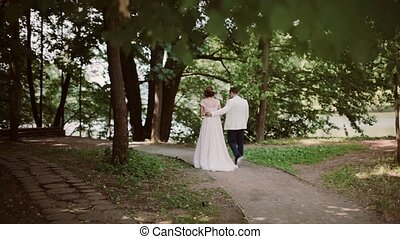 Back view of happy couple walking in park on their wedding day and kiss in the end. Beautiful white wedding dress, gown