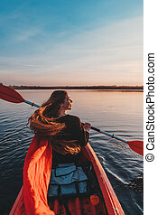 Back view of happy cute girl holding paddle in a kayak on the river