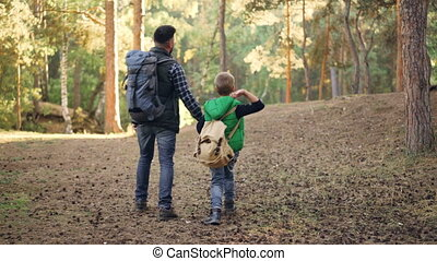 Back view of happy family child and father walking in forest with backpacks holding hands and talking, boy is throwing pine cones. Nature, fatherhood and autumn concept.