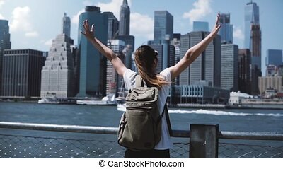 Back view of happy female tourist with backpack raising arms wide open at New York skyline view, looking back at camera.