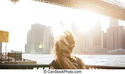 Back view of happy girl running towards river embankment, jumping, raising arms excited in New York City slow motion.