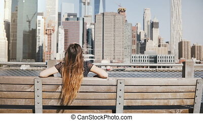 Back view of happy girl with long flying hair enjoying amazing Manhattan skyline view sitting on a bench arms wide open.