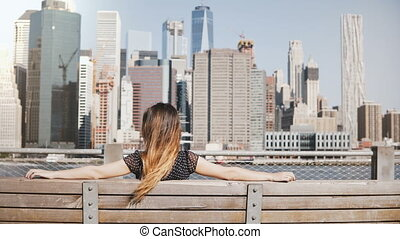 Back view of happy girl with long hair enjoying beautiful Manhattan skyline view in New York sitting with arms on bench.