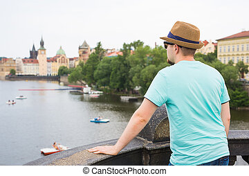 Back view of happy stylish tourist on Charles Bridge, Prague, Czech Republic. Handsome man travelling in Europe.