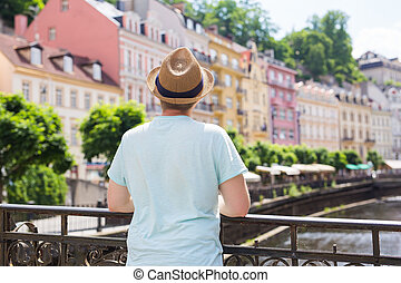 Back view of happy stylish tourist on Czech Republic. Handsome man travelling in Europe.