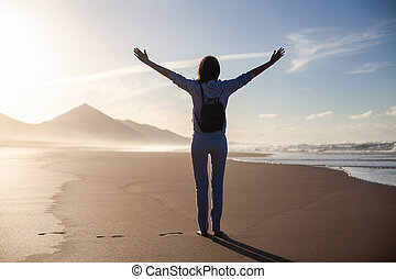 Back view of happy woman with hands up enjoy ocean beach