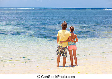 back view of happy young couple having fun on the beach. honeymoon
