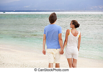back view of happy young couple holding hands on the beach. honeymoon