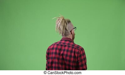 Back view of hipster man with dreadlocks pointing finger -...