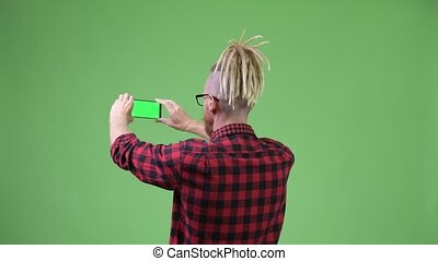 Back view of hipster man with dreadlocks taking picture with...