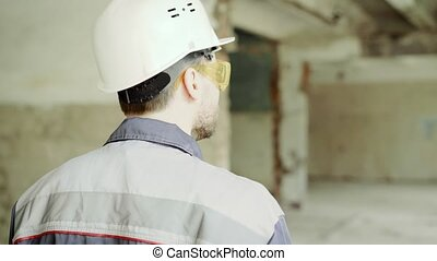 Back view of inspector dressed in uniform, protective hardhat and eyeglasses walking on the building site and checking industrial project. Professional surveyor is inspecting construction area.