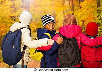 Back view of international kids standing close