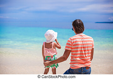 Back view of little girl and young father looking at the sea