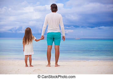 Back view of little girl hugging with dad on the beach