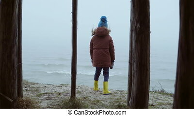 Back view of little girl in rubber boots standing on shore of the ocean and looking on waves. Child in fog and cold day.