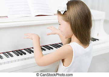 Back view of little girl in white dress playing piano