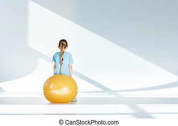 Back view of little girl sitting and exercising on fitness ball