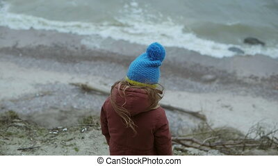 Back view of little girl standing on the shore of the sea in cold weather. Alone child looking on the waves and dreaming