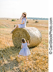 Back view of little pretty girl in wheat field at summer sunset evening, walking to her pretty mother in straw hat and dress sitting on hay stack on the background. Family, happiness, summer vacations