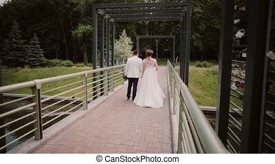 Back view of lovers walking on a bridge in a park. Bride and groom have good time on their wedding day.