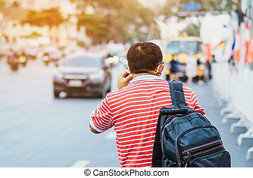 Back view of male patient with mask in red and white shirt with a black backpack standing at bus stop and waving his hand for Taxi or Bus in the city to go to the hospital.