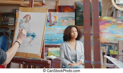 Back view of man and woman painting portraits of cute mixed race girl model