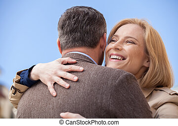 back view of man hugging happy woman outside. Smiling blond...