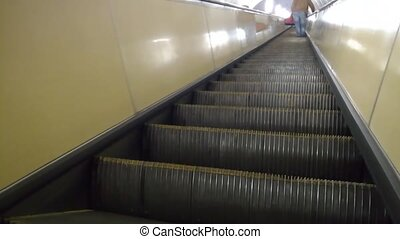 Back view of man is climbing an escalator in the subway.