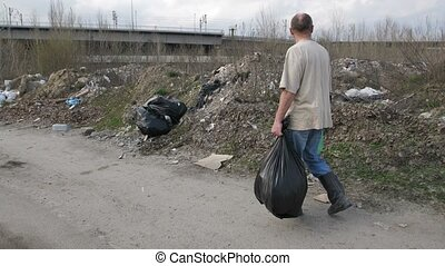 Back view of man looking for plastic at landfill - Back view...