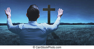 Back view of man raising hand while praying to god over...