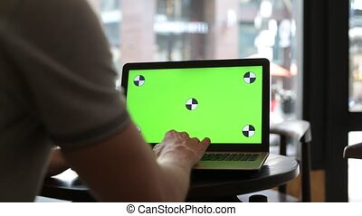 Man Using Laptop Computer With Green Screen In Restaurant