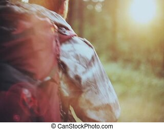 Back view of man with backpack in camouflage unionalls walking through the forest alone. Hunter exploring the territory.