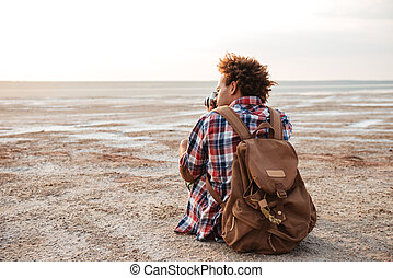 Back view of man with backpack taking photos on beach