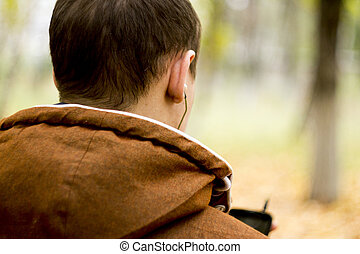Back view of man with headphones holding mobile smart phone