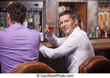 back view of men sitting at counter. waist up of two friends sitting in bar and drinking whisky