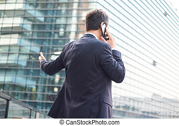 Back view of modern businessman in the city