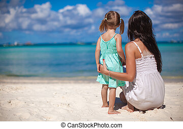 Back view of mother and his little daughter looking on the...