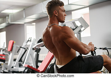 Back view of muscular man trains on simulator