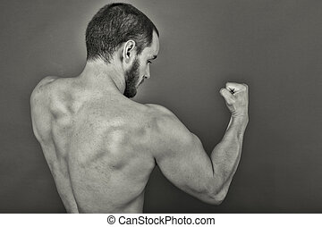 Back view of muscular young man showing his muscles