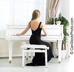 Back view of musician sitting and playing piano
