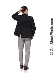 back view of pensive businessman holding head while standing